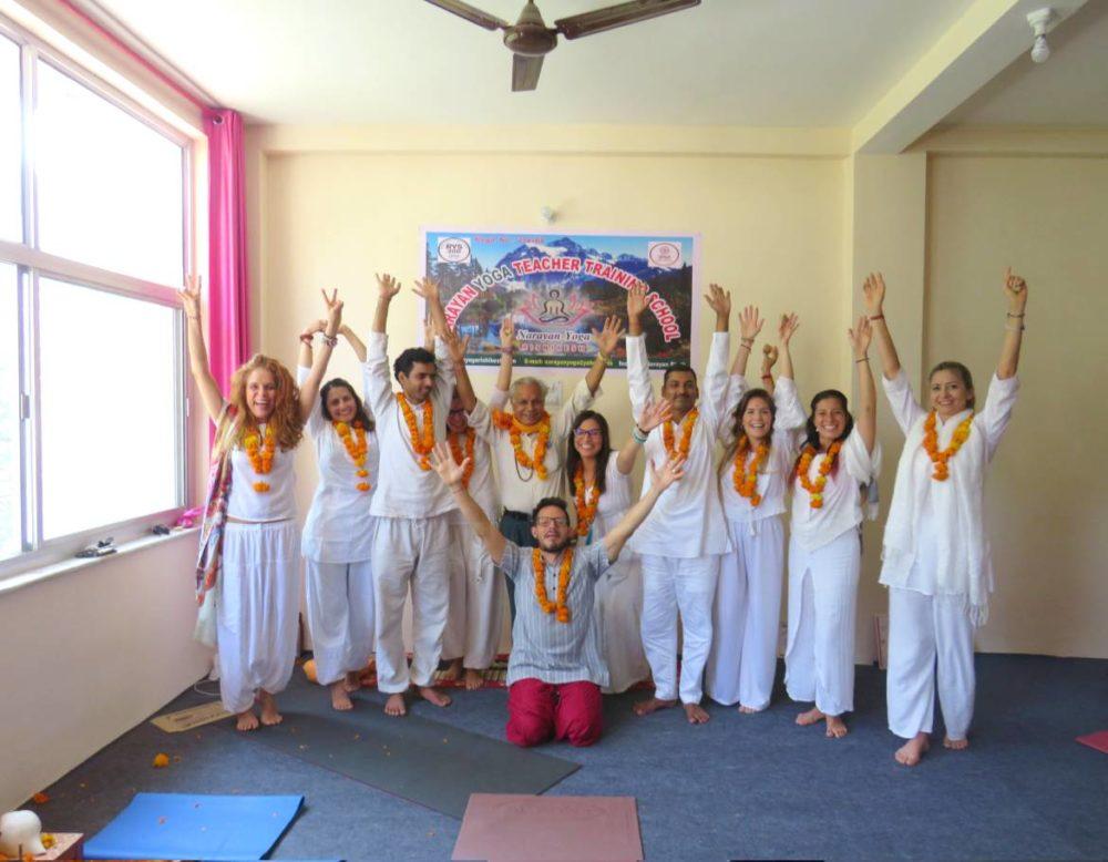 pople in white cloths cheering at narayan yoga rishikesh india
